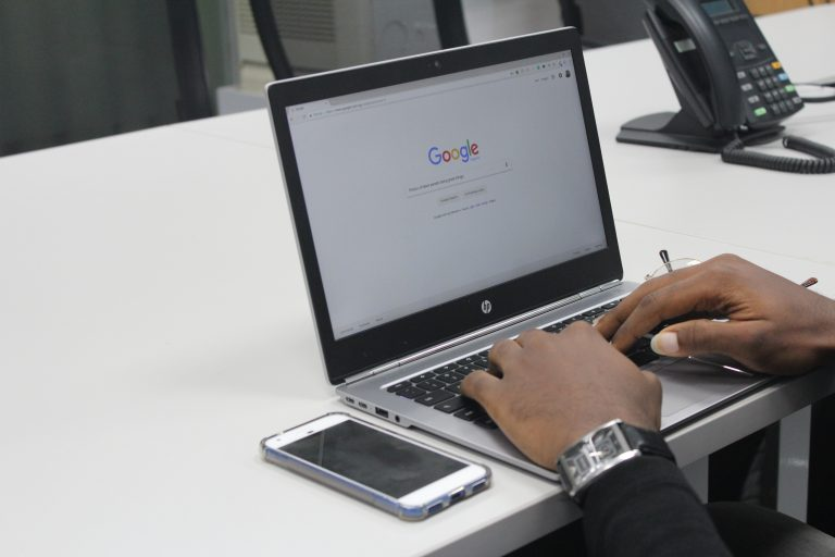 man with phone and laptop searching on google - patient pipeline